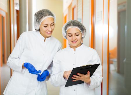 Glad doctors describing beauty procedures in aesthetic medicine center Standard-Bild