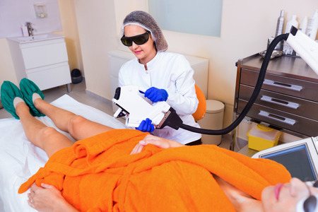healthcare visitor: Diligent  smiling female client doing laser hair removal from legs Stock Photo