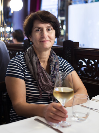 expects: Woman sits at table at restaurant and holds glass with wine