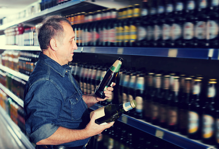 pensioner: Pensioner selecting a beer at the grocery store