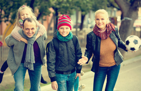 Portrait of cheerful active parents with school age children outdoors Stock Photo