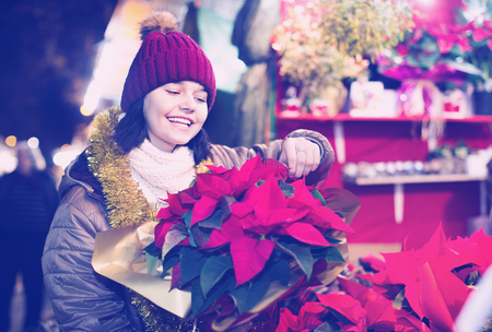 Pretty young cheerful positive girl buying floral compositions at Christmas market Stock Photo
