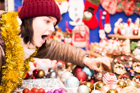 lifestile: Beautiful young american  girl choosing Christmas decoration at market