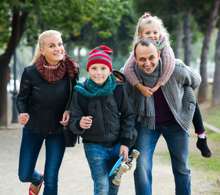 5s: positive american spouses with children posing in autumn park and smiling