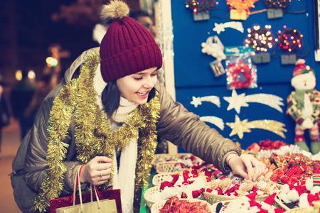 Cheerful teenage girl shopping at festive fair before Xmas