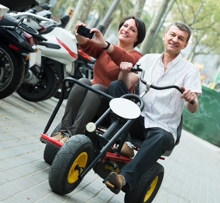 Mature couple 45-55 years old driving double bike outside and making photos