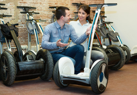 Portrait of positive smiling guy and girl making choice of segways ot rental store
