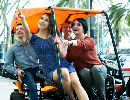 grand sons: Attractive couple with adult children sitting in grand tour electric of Europenian city Stock Photo
