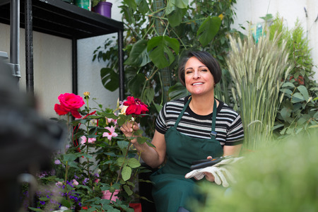 cheerful  happy woman florist holding horticultural tools in gardening counter