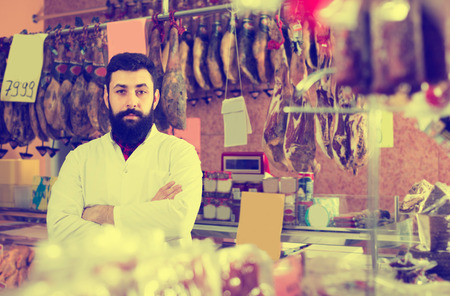 sorts: Male shop assistant demonstrating sorts of meat in butcher's shop indoors Stock Photo