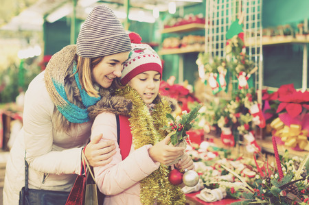spanish woman: positive spanish  woman with daughter looking at floral decoration at Cristmas fair Stock Photo
