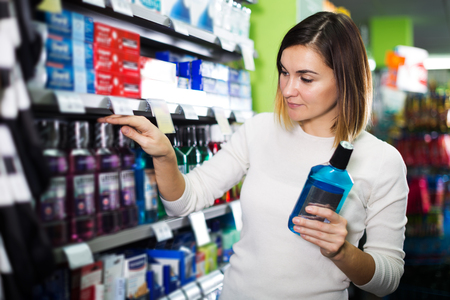 Female shopper searching for mouthwashes in supermarket