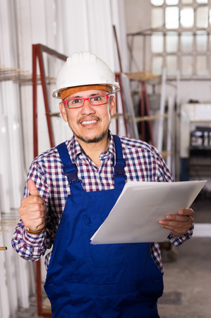 adult happy male surveyor in coverall doing checkup and filling papers Stock Photo