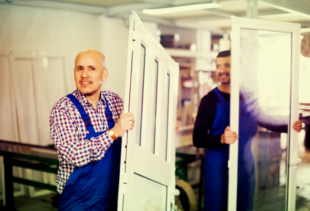 Two smiling professional workmen in coverall with different PVC windows and doors Stock Photo