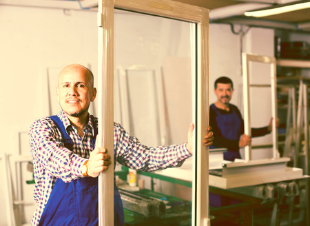 toiling: Two workmen in coveralls toiling with PVC window and door profiles at workshop