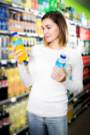 Positive young female shopper searching for beverages in supermarket