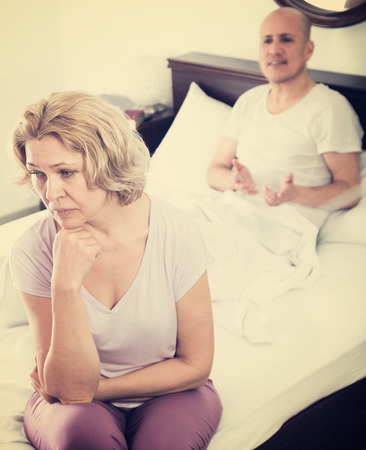 scandals: Senior man and unhappy woman getting through scandals and blamings in bedroom