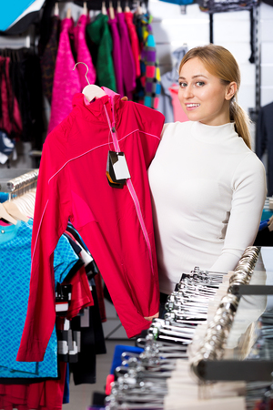25 35: Beautiful young girl choosing a sporty jacket in the store Stock Photo