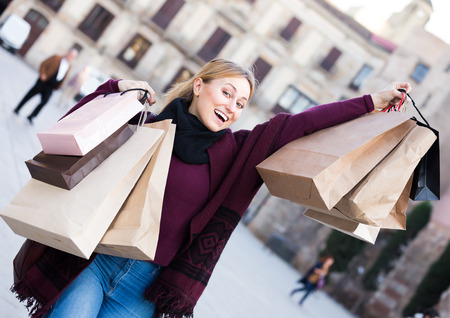 Cheerful young blond woman holding shopping paper bags at the street