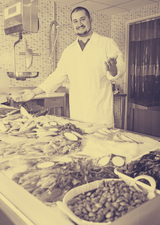 spaniard: Adult male  with beard arms folded standing near fish counter