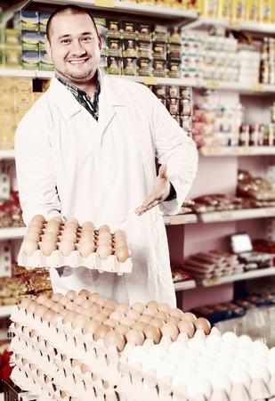 dozens: Happy seller in white robe posing with dozens of eggs