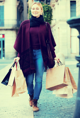 Happy blond girl looking satisfied after shopping and carrying few paper bags Stock Photo