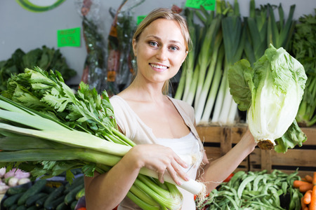 30s: smiling young woman customer 30s  buying fresh green celery and lettuce in store