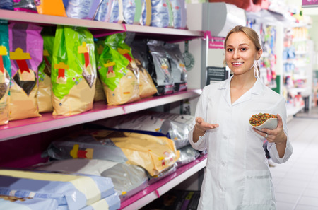 shop assistant: Female shop assistant offering food for pets in pet store