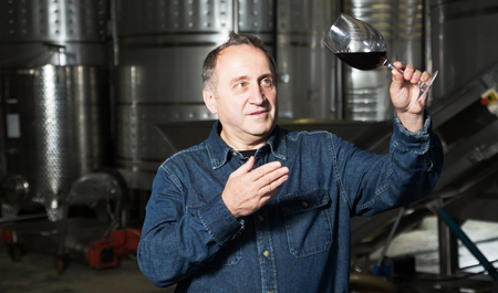 considers: Mature man considers glass with red wine on winery