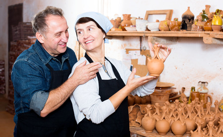 Portrait of happy potters displaying their product at the workshop Stock Photo
