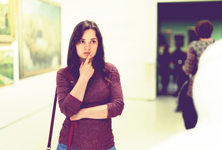 portrait of  woman watching at sculpture collection exhibition in museum