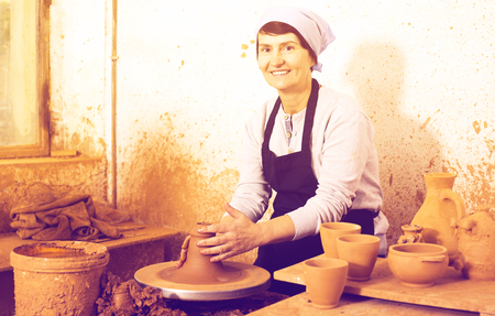 Cheerful elderly master among the pottery at the workshop Stock Photo