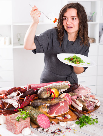 frenchwoman: European girl makes difficult choice between healthy food and tasty meat delicacies Stock Photo