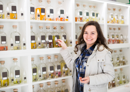 eau de perfume: Cheerful young longhaired woman choosing perfume in fragrance boutique