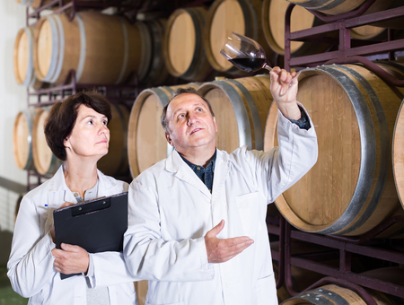 positive american  worker of winery holds glass of red wine in hand and shows him to expert