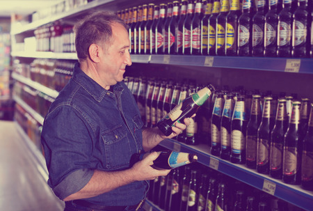 pensioner: Smiling glad pensioner selecting a beer at the grocery store Stock Photo
