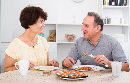 Cheerful man and woman talking and having lunch together at home Stock Photo