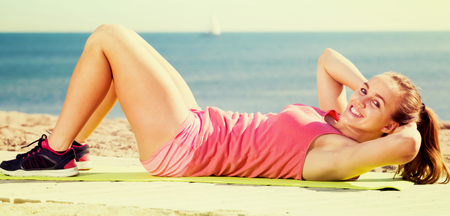 positive young female exercising on exercise mat outdoor at the seaside