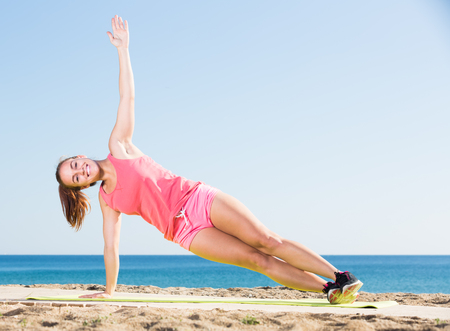 shapely young woman exercising on exercise mat outdoor at the seaside
