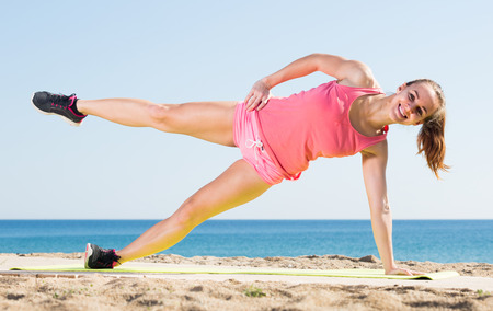 Cheerful adult  woman working out in beach