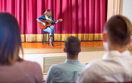 Large glad  audience enjoying guitar concert in concert hall Imagens
