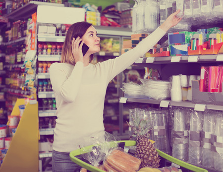 spanish woman: happy spanish woman consulting on phone about shopping in supermarket