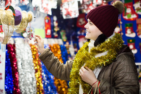 overspending: Cheerful teen  girl near the customer counter with Christmas decoration
