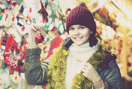happy russian  girl choosing Christmas decoration at market Stock Photo