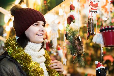 Smiling teenage girl in coat posing at Xmas market Stock Photo