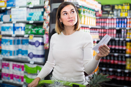 woman customer looking at notes in shopping list in supermarket