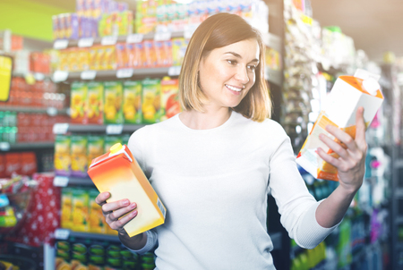 Young cheerful woman choosing refreshing beverages in supermarket Stock Photo