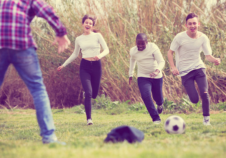 vehemence: Portrait of  laughing four friends posing on countryside field with ball in sunny day