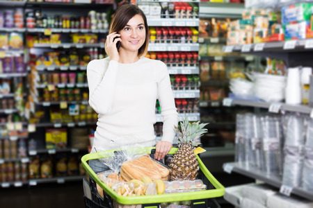 substantial: Smiling young girl customer telephoning to consult about shopping in supermarket Stock Photo