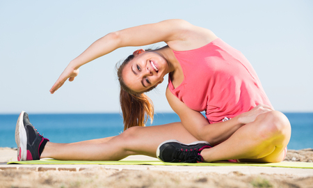 Cheerful caucasian young woman working out in beach